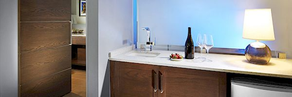 Convenience of a wet bar with sink next to the microwave and refrigerator.